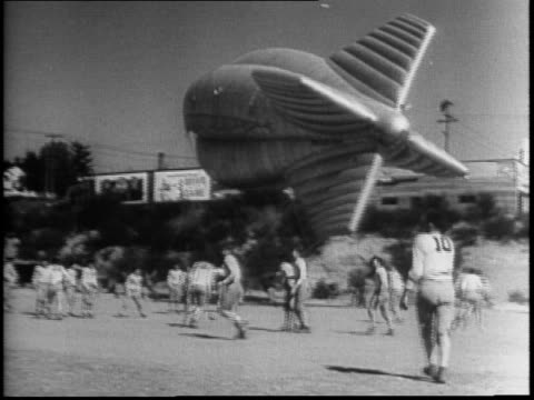 barrage balloons shaped like blimps are in the sky british call them floating elephants / men on the ground handle ropes tied to the a balloon /... - handle stock videos and b-roll footage