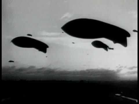 barrage balloons silhouettes floating in dawn sky balloons lowering single balloon descending behind aleksandr pushkin monument statue in moscow. the... - ta ner bildbanksvideor och videomaterial från bakom kulisserna