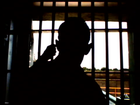 barred csp prison windows ms back silhouette of unidentifiable inmate behind window bars looking out windows co trapped trap prisoner detainee... - prison cell stock videos & royalty-free footage