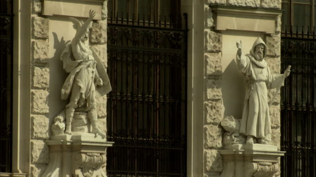 barred windows are flanked by stone statues. available in hd. - the hofburg complex stock videos & royalty-free footage