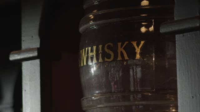 vídeos de stock, filmes e b-roll de a barrel labeled whisky sits between wooden posts. - barril