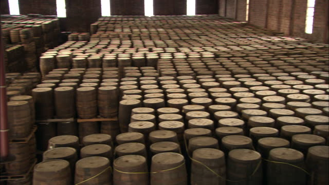 barrels of rum fill a warehouse. - rum stock videos and b-roll footage