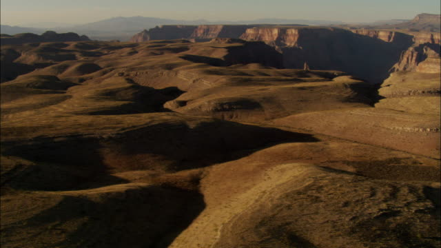 barren hills cover a plateau above the grand canyon. - schlucht stock-videos und b-roll-filmmaterial