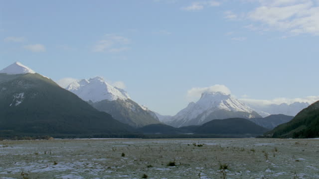 WS A barren prairie and snow capped mountain peaks under a partly cloudy sky