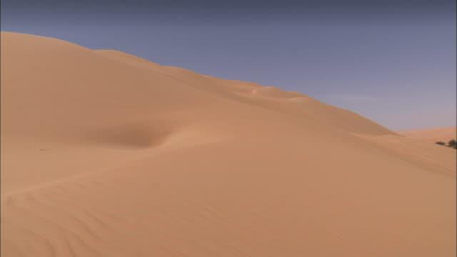 vídeos y material grabado en eventos de stock de barren sand dunes surround a desert oasis. available in hd. - oasis desierto