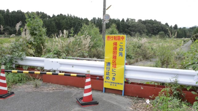 a barricade and a guard rail stands in front of a path leading to the difficulttoreturn zone in namie fukushima prefecture japan on wednesday oct 5 a... - abandoned stock videos & royalty-free footage