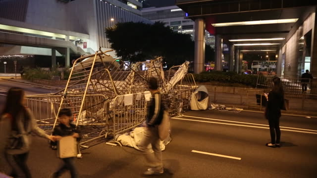 barricades for occupy hong kong protesters in hong kong china on december 10 wide shots and close ups of pedestrians walking by piles on barriers on... - occupy central stock videos & royalty-free footage