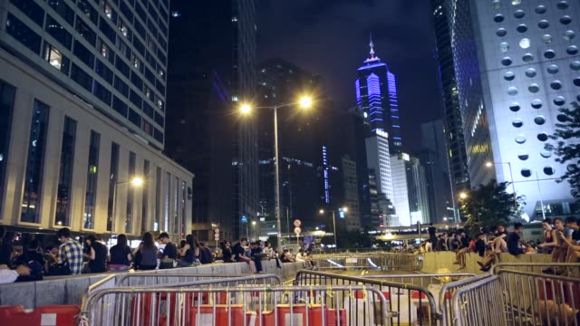 barricades stand in a road near the central government office at night in hong kong china on wednesday oct 1 tilt up from barriers to skyscraper... - time's up social movement stock videos and b-roll footage