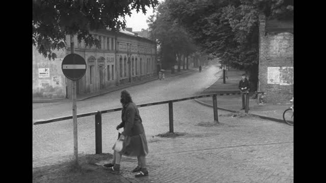 """barrier across street, boys standing with bicycles beyond barrier, sign saying """"berlin"""" / automobile stopped behind barrier, two policemen standing... - boys beware点の映像素材/bロール"""