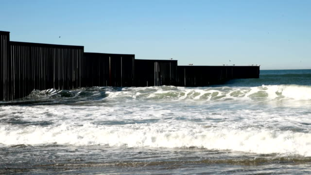 barrier runs into the pacific ocean as it separates the united states and mexico at border field state park on january 23, 2019 in san diego,... - us state border stock videos & royalty-free footage