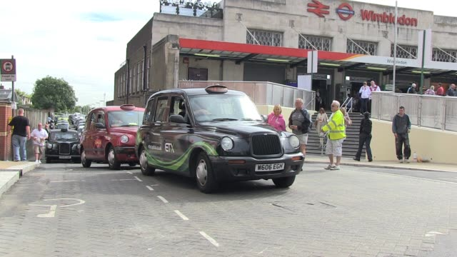 barriers to guide the thousands of expected spectators are in place and lines of taxis wait at wimbledon train and tube station on day one of... - taxi stock videos & royalty-free footage