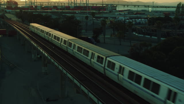 bart trains, oakland cranes, san francisco skyline - baia di san francisco video stock e b–roll