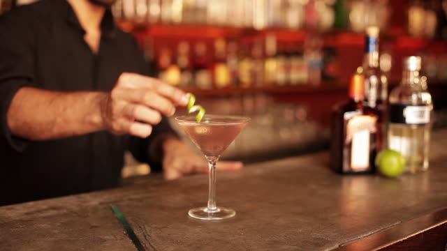 bartender adding finishing touch to cosmopolitan - garnish stock videos & royalty-free footage