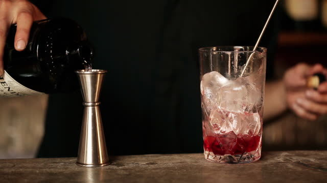 Bartender adding gin to cocktail