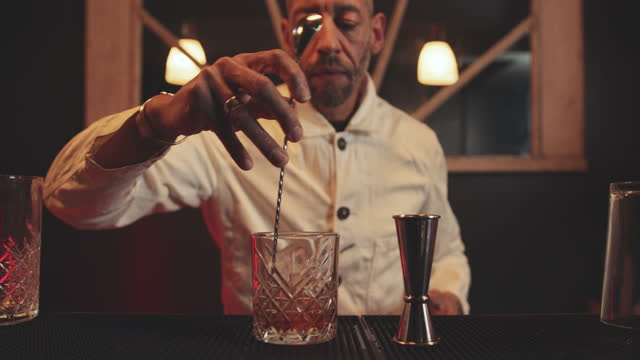 bartender adding ice cubes and stirring in cocktail glass, making cocktail in speakeasy bar - 混ぜる点の映像素材/bロール