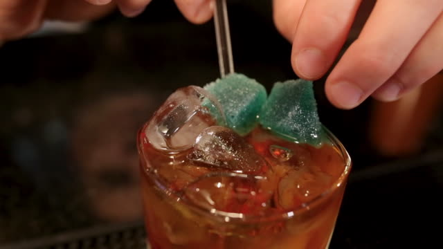 vídeos de stock e filmes b-roll de bartender adding jelly tots to delicious cocktail on bar counter in night club - coinfeitos
