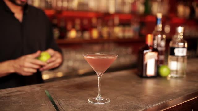 bartender adding lime peel garnish to cosmopolitan - garnish stock videos & royalty-free footage