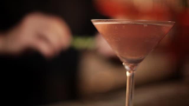vídeos y material grabado en eventos de stock de bartender adding lime rind garnish to cosmopolitan - perfección