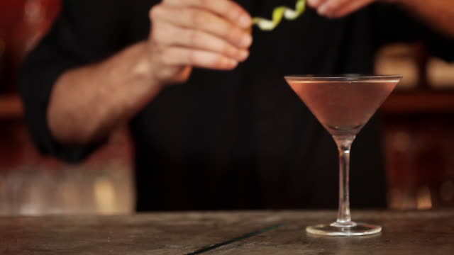 Bartender adding lime rind garnish to cosmopolitan