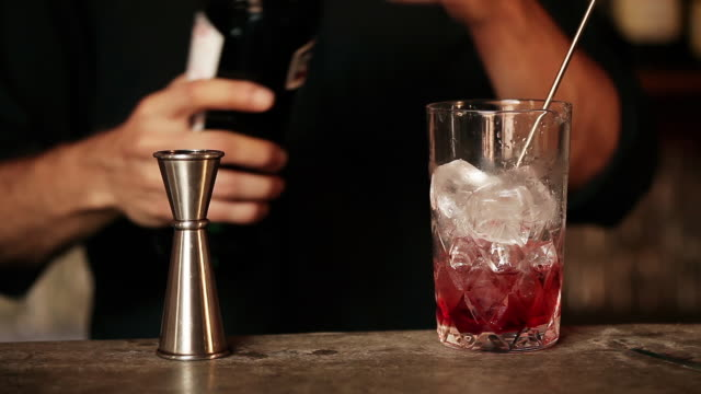 Bartender adding vermouth to cocktail