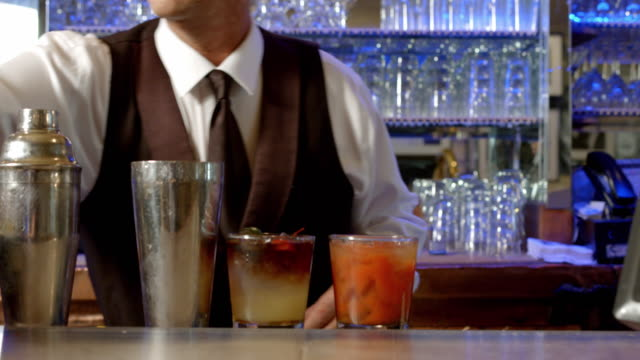 vídeos de stock, filmes e b-roll de ms bartender adds garnish to finished cocktails - vest