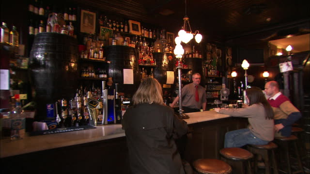 bartender and customers at bar in pub, northern ireland - bar stock videos & royalty-free footage
