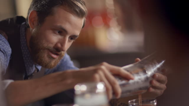 Bartender chats with customer while pouring drink into glass from cocktail shaker