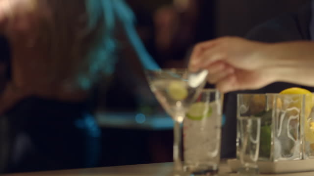 ms bartender drops olive into martini glass - bartender stock videos and b-roll footage
