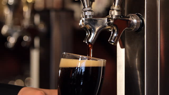 A bartender fills a beer glass clear up to the top.