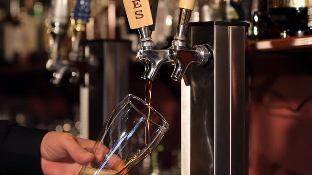 A bartender fills a glass from a beer tap.
