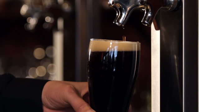 a bartender fills a glass with beer from a tap. - serving food and drinks stock videos & royalty-free footage