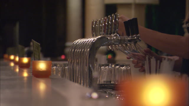 a bartender fills a glass with beer. - refreshment stock videos and b-roll footage