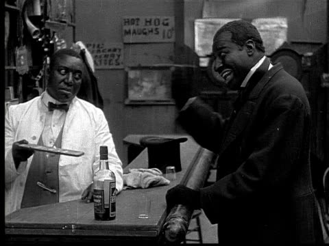 1916 MS B&W bartender forcing man to add drink to his running bar tab on chalkboard
