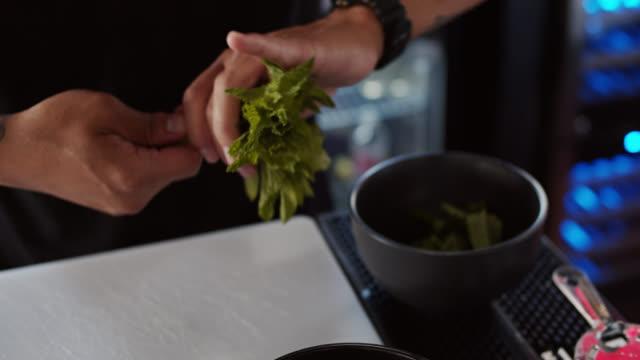 Barman Rassemblant des brins de menthe