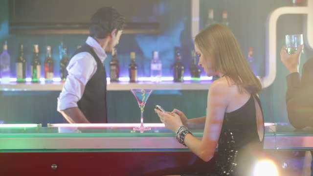 Bartender giving mocktail drink to a young woman in a bar