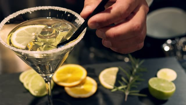 bartender hand adding straws to martini - close up - martini stock videos & royalty-free footage