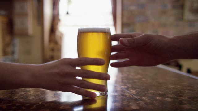 a bartender hands a beer to someone across a bar counter at a bar - reaching stock videos & royalty-free footage