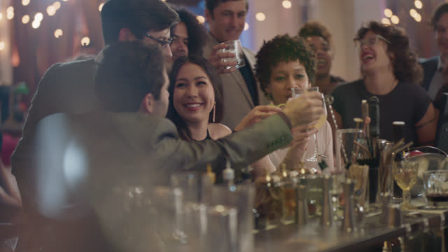 vidéos et rushes de a bartender hands a woman sitting at the bar a drink, her friends all toast - bar