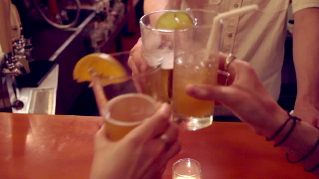 A bartender has a toast with customers at a bar.