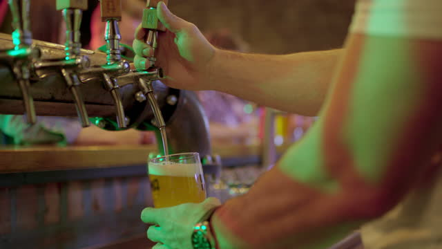 bartender holding a pint and pouring draft beer for people at the bar counter - lager stock videos & royalty-free footage