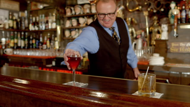 vídeos de stock e filmes b-roll de bartender in soft-focus background pours wine into glass and walks it over to customer as he places it next to a cocktail on bar counter - camisa e gravata