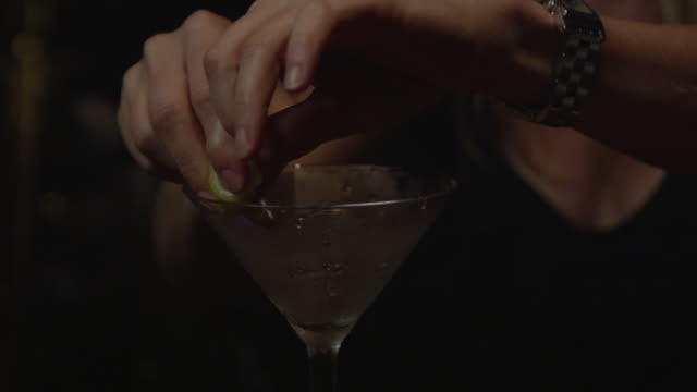 a bartender lines the rim of a martini glass with a lemon rind. - citrus fruit stock videos & royalty-free footage