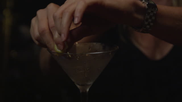 bartender lining rim of martini glass with lemon rind - martini glass stock videos and b-roll footage
