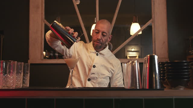 bartender making a cocktail at bar in drink establishment - bar drink establishment stock videos & royalty-free footage