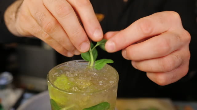 bartender making delicious cocktail on bar counter in night club, putting mint on top of it - aperitivo video stock e b–roll