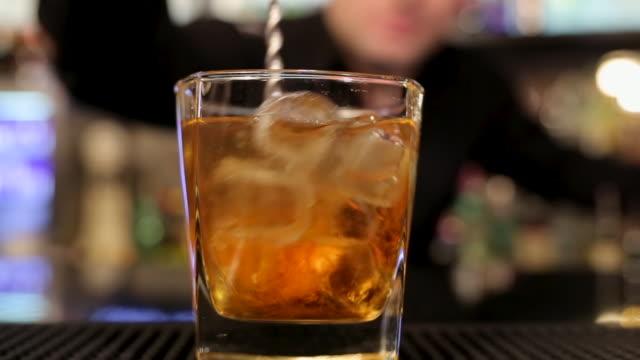 vídeos y material grabado en eventos de stock de bartender haciendo delicioso cóctel con whisky en el mostrador del bar en el club nocturno - servicio
