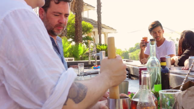 bartender making drinks at pool party - bartender stock videos & royalty-free footage