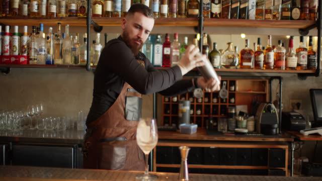 vidéos et rushes de barman faisant la boisson mélangée - shaker