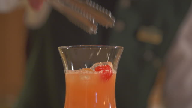 a bartender mixes a drink and puts a cherry on top. - blickwinkel der aufnahme stock-videos und b-roll-filmmaterial