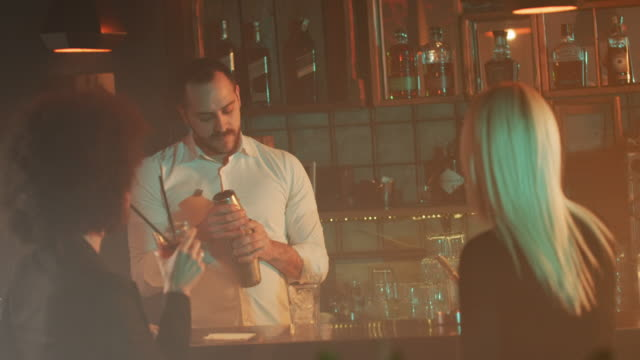 Bartender mixing and pouring drink 4K